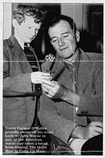Cormac O'Malley (age 8) shows his scout knife to actor John Wayne, 1951